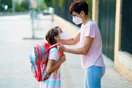 Mother preparing her little girl for the return to school wearing a mask