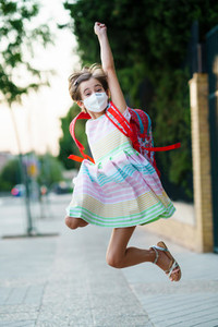 Girl wearing a mask takes a jump for joy at going back to school