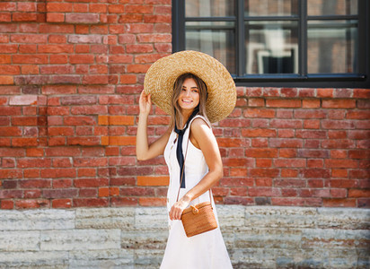 Young happy woman holding hat