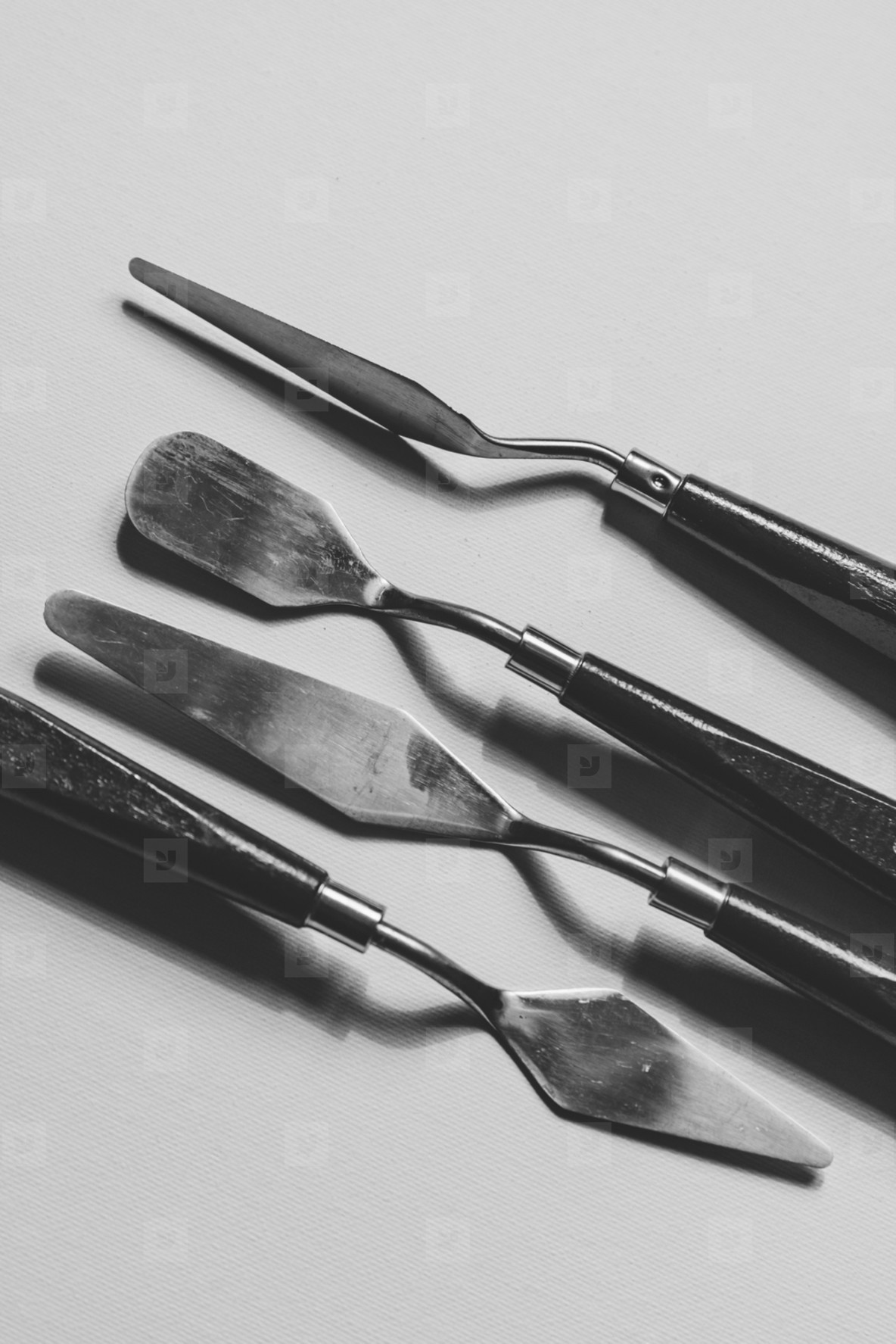 Black and white photography of palette knives over the blank canvas