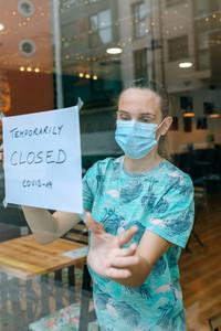 Woman placing coronavirus closure sign