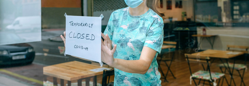 Woman placing coronavirus closure sign