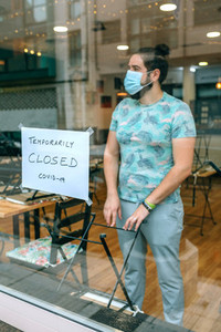 Man behind the glass of his restaurant closed by covid 19
