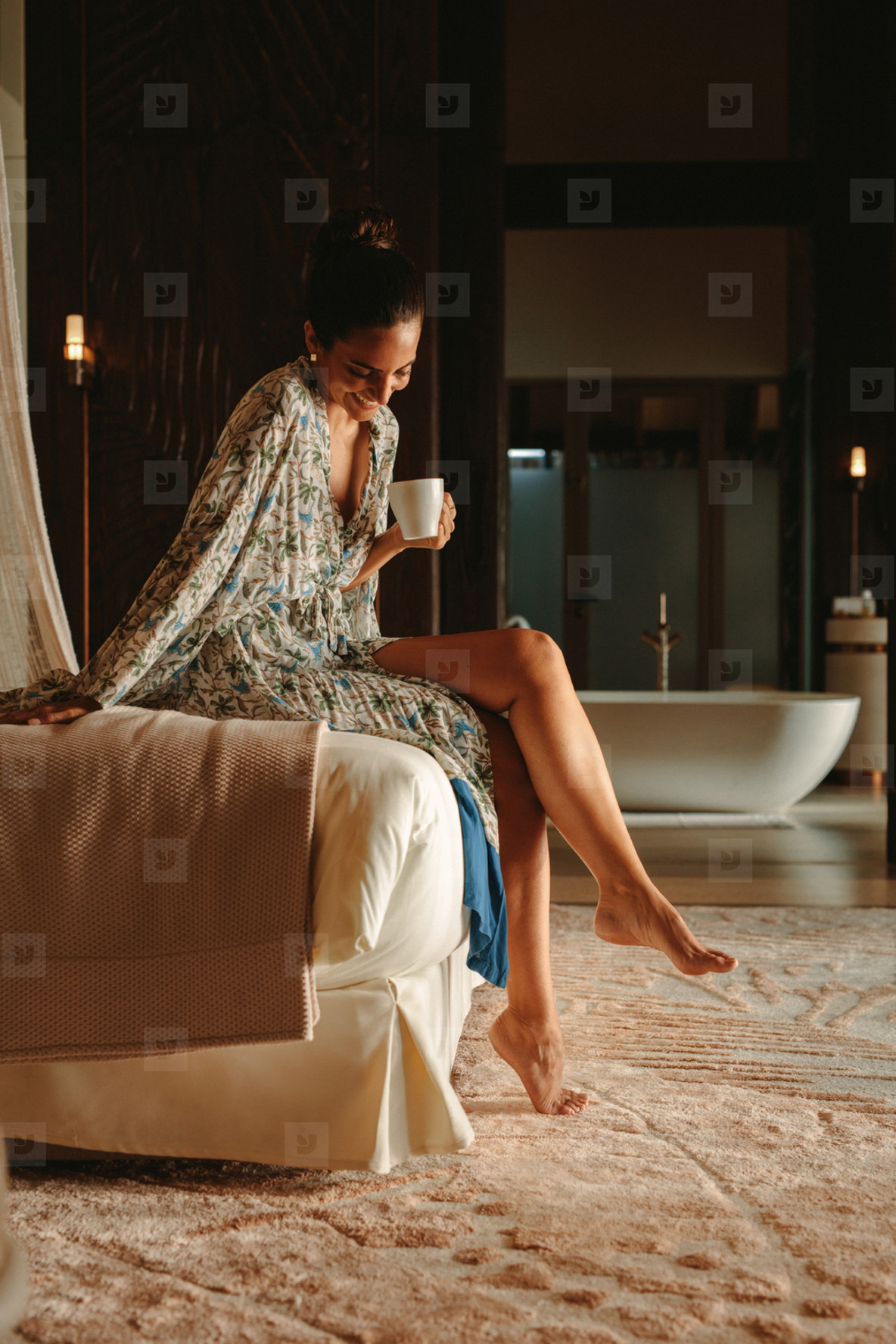 Woman enjoying coffee sitting on bed