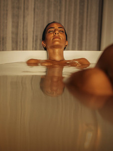 Woman relaxing in bathtub