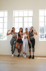 Fit women showing muscles at a fitness studio