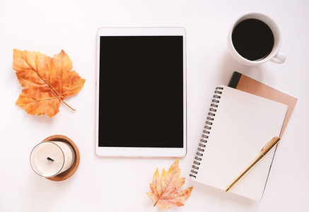 Flat lay of workspace desk on autumn leaves background with blan