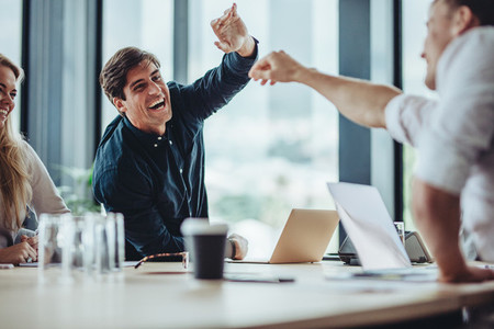 Businesspeople excitedly high fiving together in meeting