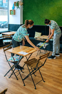 Workers measuring social distance between tables
