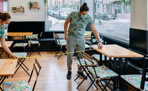 Workers measuring social distance between tables