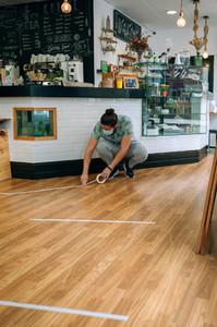Coffee shop worker putting floor marks