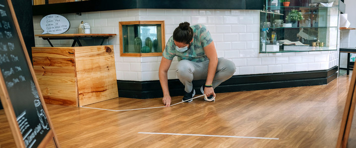 Coffee shop worker putting floor marks