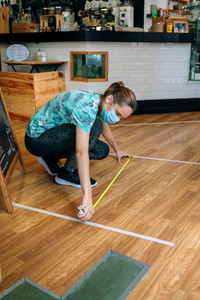 Coffee shop worker measuring floor marks