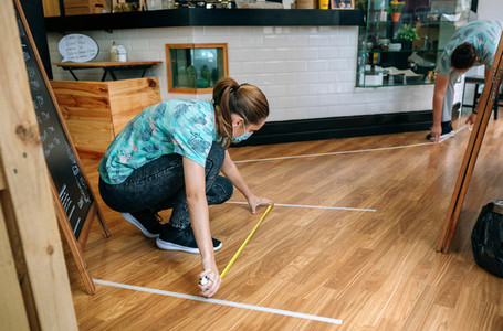 Coffee shop workers measuring floor marks
