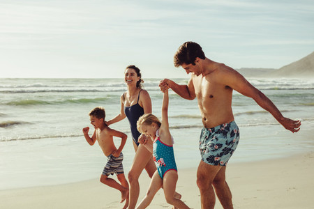 Playful family enjoying playing at beach during vacation