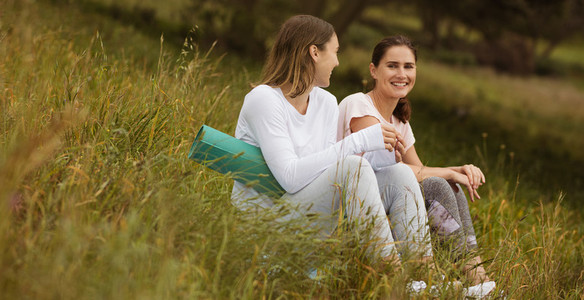 Fitness women sitting in park and talking