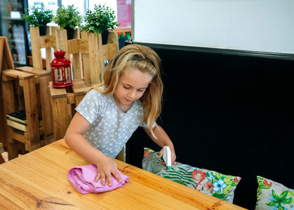 Girl disinfecting table due to coronavirus