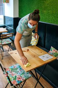 Waiter disinfecting tables due to coronavirus