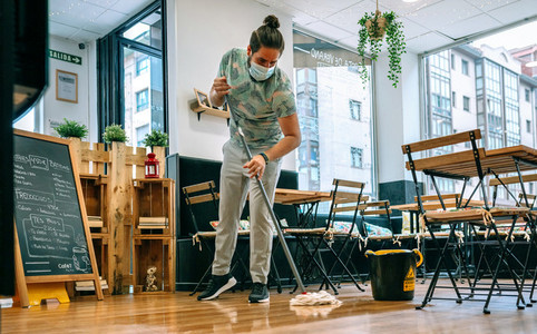 Worker mopping the floor of a restaurant