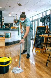 Worker mopping the floor of a coffee shop