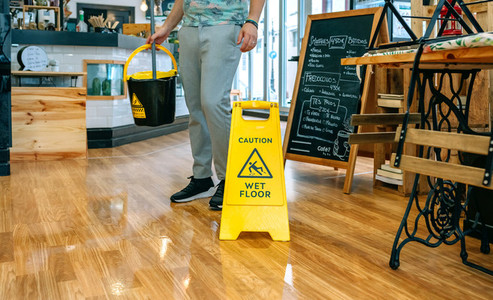 Worker placing wet floor sign after mopping