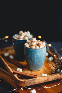 Hot chocolate with marshmallows and cinnamon in blue ceramic cups on a table  The concept of cozy holidays and New Year