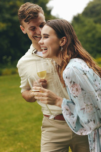 Cheerful couple at the park with champagne