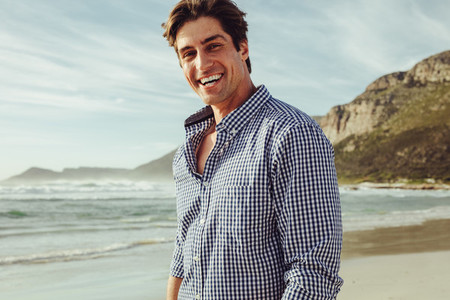 Handsome man smiling on the beach