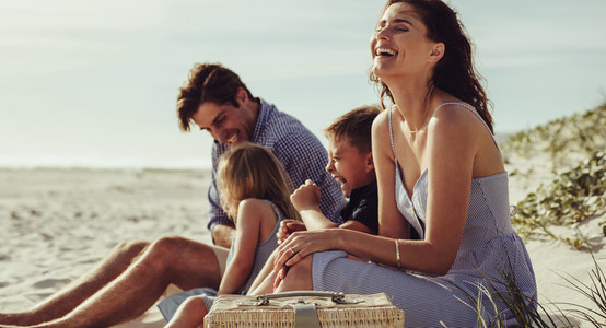 Family sitting on the beach and having fun