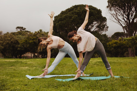 Women practising yoga in a park