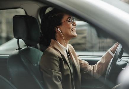 Businesswoman enjoying music while driving to work