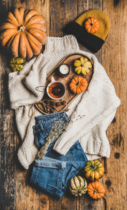 Flat lay of fall trendy women apparel layout over rustic background