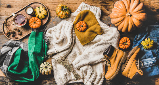 Flat lay of fall trendy women outfit layout over wooden background