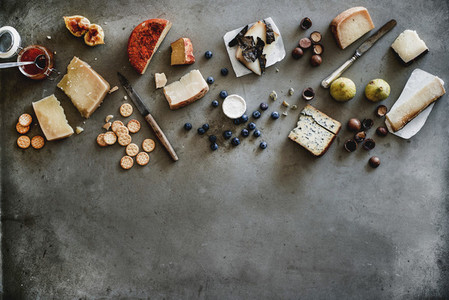 Variety of wine snacks jam and cheeses over grey background