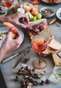 Rose wine  cheese  charcuterie  appetizers and mans hands with food