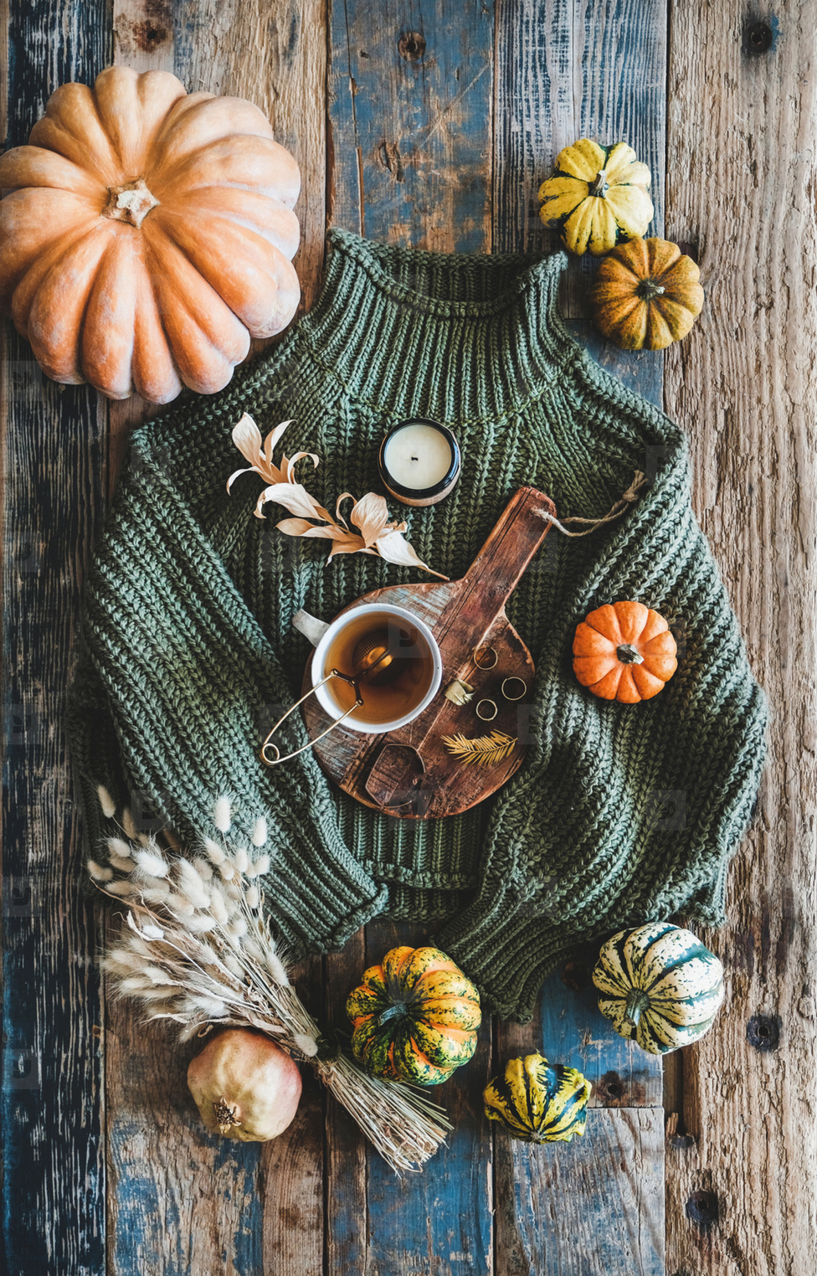 Green sweater and accessories over rustic wooden background  top view