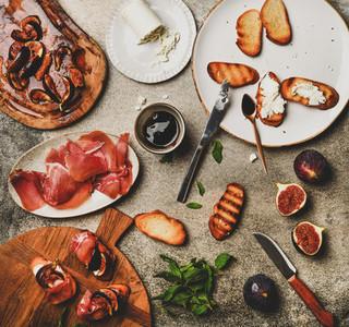 Crostini with prosciutto  cheese and figs over concrete table