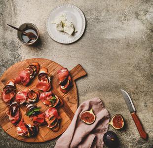 Crostini with prosciutto cheese figs over concrete table copy space