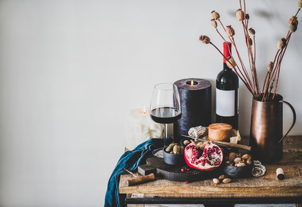 Red wine and different snacks on wooden board copy space