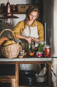 Young blond woman in apron cooking vegetables preserves in kitchen