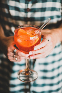 Young woman holding glass of Aperol spritz cold drink