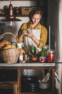 Young blond woman in linen apron cooking homemade vegetable preserves