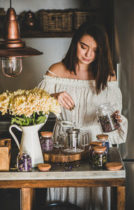 Young woman adding dried flowers for brewing tea in pot