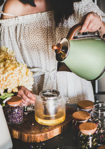 Young woman brewing grean tea in glass pot in kitchen