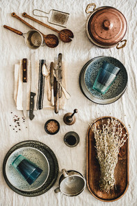 Various kitchen utensils and tablewear over linen tablecloth vertical composition