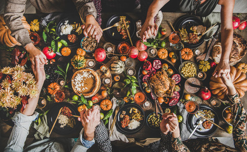 Family or friends praying holding hands at Thanksgiving celebration table
