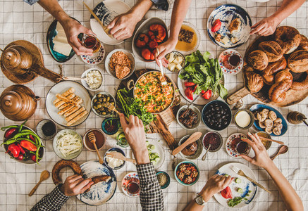 Flat lay of family having Turkish breakfast over chekered linen tablecloth