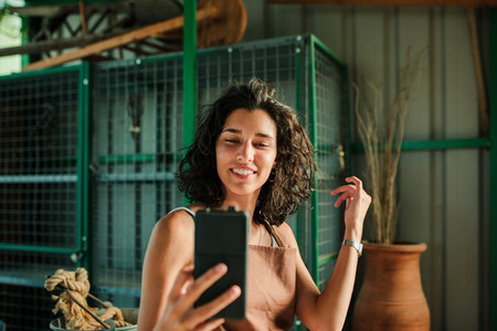 Woman taking a selfie in her small ceramic shop