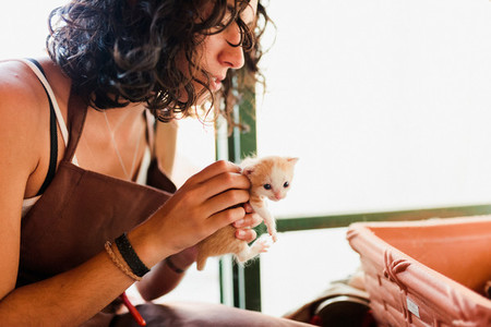 Woman with small kittens inside her store