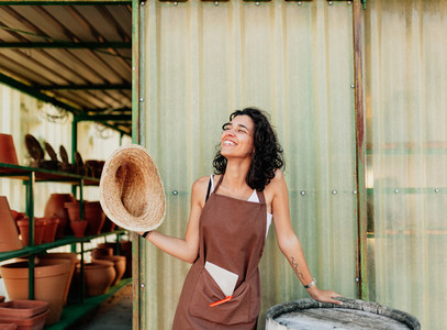 Woman fans herself with her straw hat at the door of her ceramic business
